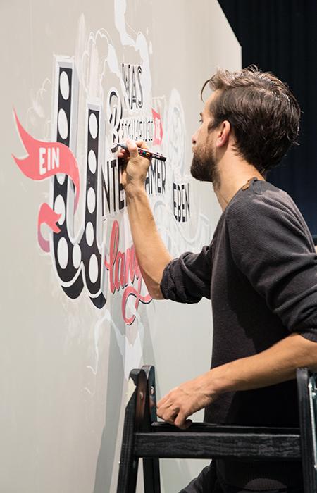Mathias Truniger – der Tafelmaler – bei der Arbeit. Kreidetafel, Schriftenmalerei, sign painting, Schaufensterbeschriftung, Wandbeschriftung, hand gemalt, Tafelbeschriftung, Tafelmaler, reverse glass painting, mural