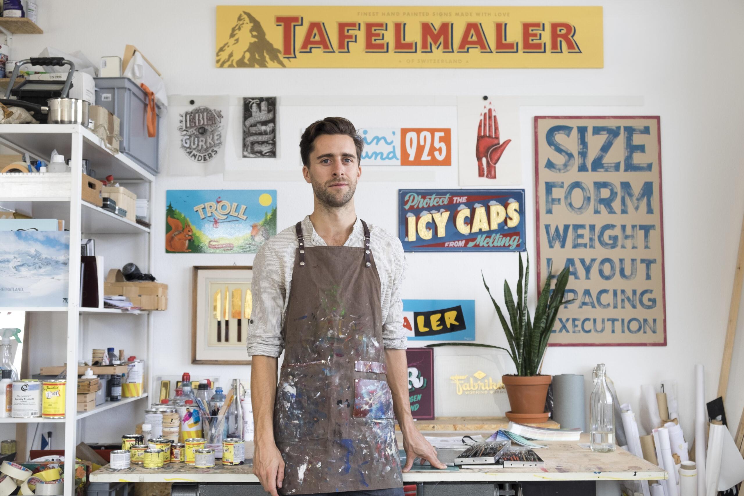 Der Tafelmaler Mathias Truniger in seinem Atelier in Zürich. Er ist ein traditioneller Schriftenmaler und Illustrator. Typografie, Design, Logo, Schriftgestalter, Schildermaler, sign painter, sign painting, hand lettering, mural, muralist, gold leaf, gilding, glass gilding, reverse glass gilding, Hinterglasvergoldung